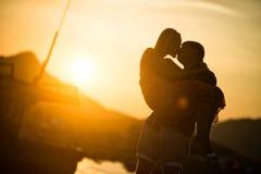 Coppie nell'amore che bacia al tramonto Siluetta immagine stock