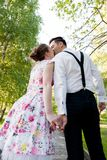 Coppie nell'amore che bacia e che si tiene per mano nel parco di estate Fotografia Stock Libera da Diritti