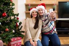 Coppie nell'amore che fa selfi accanto all'albero di Natale Fotografie Stock Libere da Diritti