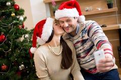 Coppie nell'amore che fa selfi accanto all'albero di Natale Immagini Stock