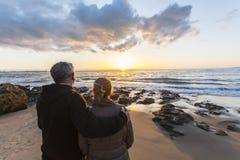 Coppie nell'amore che guarda un tramonto sulla spiaggia Immagini Stock