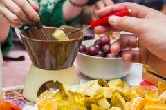 Coppie nell'amore che mangia la fonduta di cioccolato con frutta Fotografie Stock
