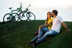 Coppie nell'amore che riposa sul prato verde Immagine Stock
