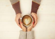 Coppie nell'amore che si tiene per mano con la tazza dell'immagine di vista superiore del coffe su fondo di legno bianco L'uomo t Fotografie Stock Libere da Diritti