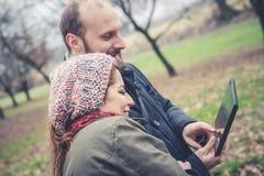 Coppie nell'amore facendo uso del wifi di collegamento della radio di web della compressa Fotografia Stock Libera da Diritti