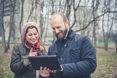 Coppie nell'amore facendo uso del wifi di collegamento della radio di web della compressa Immagini Stock