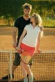 Coppie nell'amore Le coppie nell'amore stanno alla rete del tennis sul campo in argilla fotografia stock libera da diritti