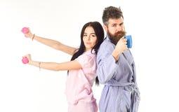 Coppie nell'amore in pigiama, supporto dell'accappatoio isolato su fondo bianco Coppie, famiglia sui fronti sonnolenti, pieni di  Fotografie Stock