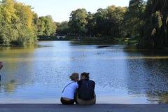 Coppie nell'amore sulla riva dello stagno fotografia stock