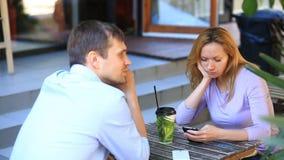 Coppie nell'amore in un caffè all'aperto Uomo e bella donna ad una data Ognuno sta esaminando il suo telefono cellulare video d archivio