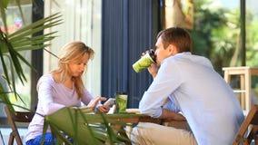 Coppie nell'amore in un caffè all'aperto Uomo e bella donna ad una data Ognuno sta esaminando il suo telefono cellulare stock footage