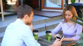 Coppie nell'amore in un caffè all'aperto Uomo e bella donna ad una data Ognuno sta esaminando il suo telefono cellulare archivi video