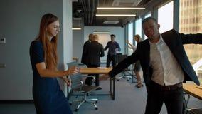 Coppie nell'ufficio di affari che balla dopo la conquista della celebrazione di affare archivi video