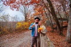 Coppie nella foresta di autunno, abbracciante e godente di un giorno meraviglioso fotografie stock libere da diritti