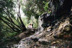 Coppie nella foresta vicino al ruscello di caduta Fotografia Stock Libera da Diritti
