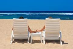 Coppie nelle presidenze di spiaggia Immagini Stock Libere da Diritti