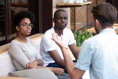 Coppie nere annoiate che si siedono sull'uomo caucasico d'ascolto dello strato immagine stock libera da diritti