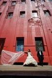 Coppie nuziali felici che stanno sul marciapiede sotto la costruzione rossa alta Immagini Stock Libere da Diritti