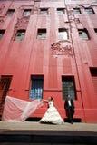 Coppie nuziali felici che stanno sul marciapiede sotto la costruzione rossa alta Fotografia Stock