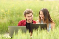 Coppie o amici che guardano i computer portatili in un campo Fotografie Stock Libere da Diritti