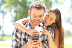 Coppie o amici che ridono con i telefoni Immagini Stock