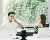 Coppie o colleghe asiatici che hanno pausa caffè mentre lavorando al computer portatile al caffè o alla caffetteria Fotografia Stock Libera da Diritti