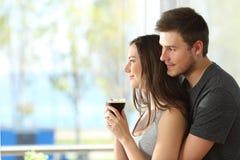 Coppie o matrimonio che guardano attraverso una finestra immagini stock
