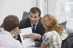 Coppie osservando opuscolo con l'agente immobiliare Immagini Stock Libere da Diritti