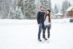 Coppie in pattini da ghiaccio che abbracciano e che esaminano macchina fotografica all'aperto Immagini Stock
