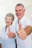 Coppie pensionate allegre che esaminano macchina fotografica che dà i pollici su Immagine Stock Libera da Diritti
