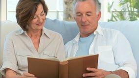 Coppie pensionate che esaminano un album di foto video d archivio