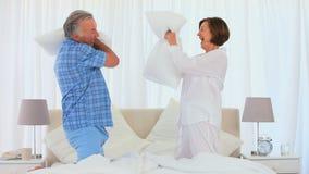 Coppie pensionate che giocano sul letto con i loro cuscini stock footage