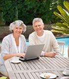 Coppie pensionate che lavorano al loro computer portatile Immagine Stock