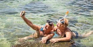 Coppie pensionate felici che prendono selfie nell'escursione tropicale del mare con la macchina fotografica dell'acqua e la masch fotografia stock libera da diritti
