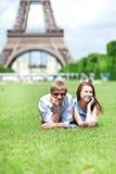 Coppie positive felici che pongono sull'erba Immagini Stock Libere da Diritti