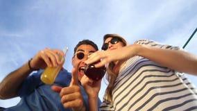 Coppie potabili divertenti che osservano giù la macchina fotografica, i cocktail beventi e ridere stock footage