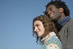 Coppie premurose che distolgono lo sguardo contro il chiaro cielo blu Immagine Stock Libera da Diritti