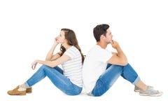 Coppie premurose che si siedono sul pavimento di nuovo alla parte posteriore Fotografie Stock Libere da Diritti