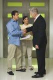 Coppie preoccupate che stringono le mani con il consulente Fotografie Stock