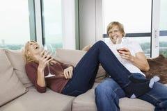 Coppie rilassate allegre con i vetri di vino in salone a casa Fotografie Stock Libere da Diritti
