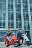 Coppie romantiche attraenti, un uomo bello e femmina sexy, stanti con due retro motorini italiani contro la a immagini stock libere da diritti