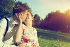 Coppie romantiche che baciano con l'amore in parco Volata delle bolle di sapone immagine stock
