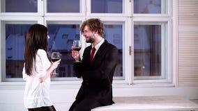 Coppie romantiche che bevono vino rosso Belle giovani coppie con i vetri di vino rosso Giovani coppie romantiche che celebrano stock footage