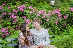 Coppie romantiche che parlano sul banco in giardino Fotografia Stock