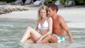 Coppie romantiche che si siedono dalla riva alla spiaggia Fotografie Stock Libere da Diritti