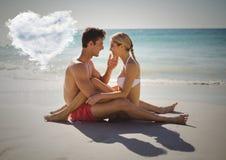 Coppie romantiche che si siedono sulla spiaggia con la nuvola del cuore Fotografia Stock Libera da Diritti