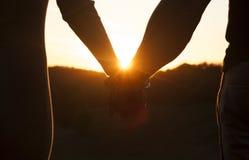 Coppie romantiche che si tengono per mano e che guardano il bello tramonto sui precedenti fotografia stock