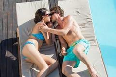 Coppie romantiche circa da baciare sulle chaise-lounge del sole Immagine Stock