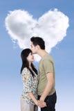 Coppie romantiche con la nuvola di forma del cuore Immagini Stock