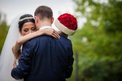 Coppie romantiche delle persone appena sposate del biglietto di S. Valentino che abbracciano in una sposa del parco Fotografie Stock